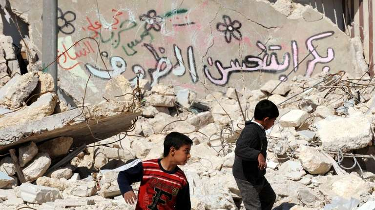 Syrian children walk past destroyed buildings in the