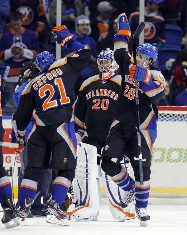 Kyle Okposo, Evgeni Nabokov and Matt Moulson celebrate