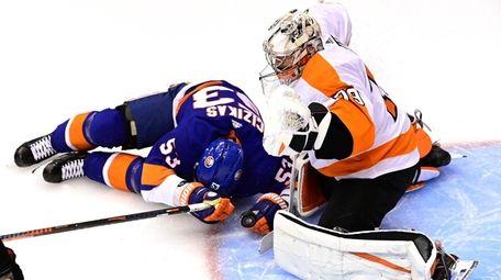 Islanders center Casey Cizikas slides into Flyers goaltender
