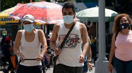 People wear masks as they cross Queens Boulevard