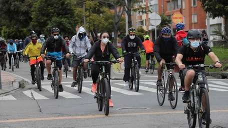 Bycicle riders wear protective masks while out exercising