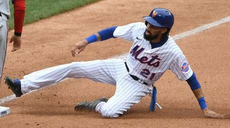 The Mets' Billy Hamilton slides into third base