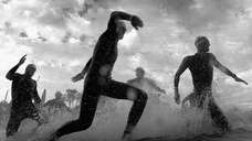 Competitors run into the water to start the