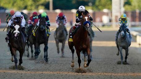 Jockey John Velazquez riding Authentic, second right, leads