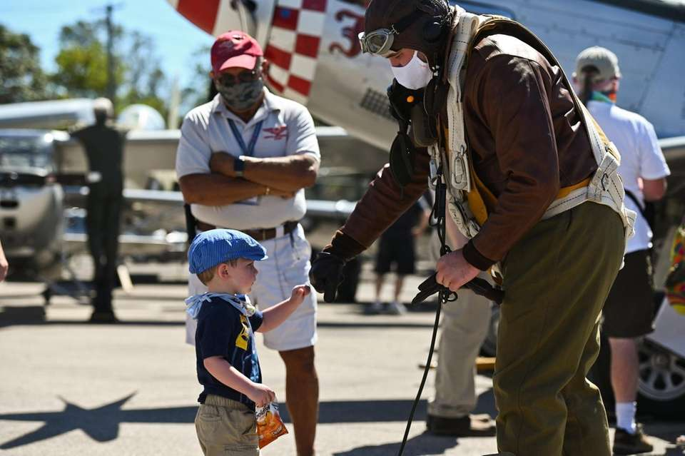 Finn Peters, 2, of Massapequa, greets re-enactor Andrew