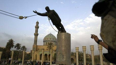 A U.S. Marine watches a statue of Saddam
