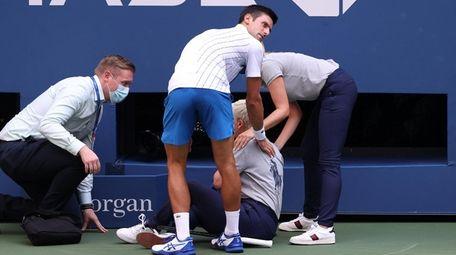Novak Djokovic of Serbia tends to a line