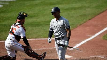 Yankees Aaron Hicks, right, reacts after striking out,