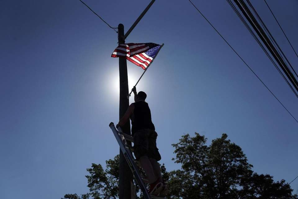Chris Johnson, of Wantagh, installs American flags on