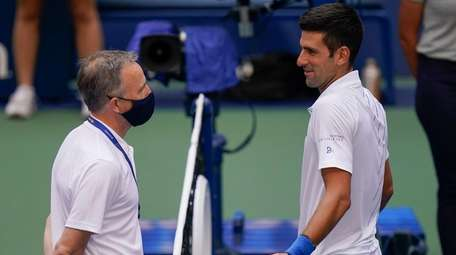 Novak Djokovic talks with the umpire after inadvertently