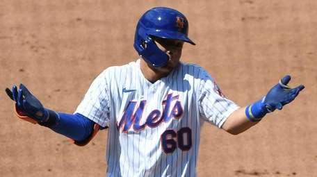 The Mets' Andres Gimenez gestures to the dugout