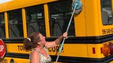 Jeanette Herman scrubs her school bus in preparation