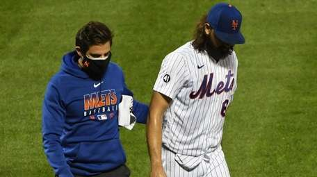 A trainer assists reliever Robert Gsellman off the