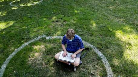 A student sits inside a painted circle during