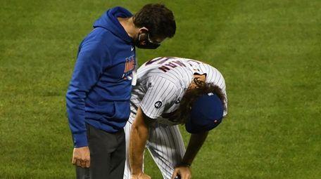 Mets relief pitcher Robert Gsellman bends over in