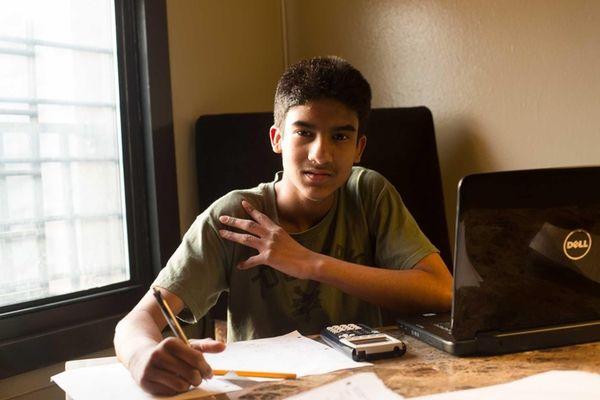 Santiago Munoz sits behind his new desk in