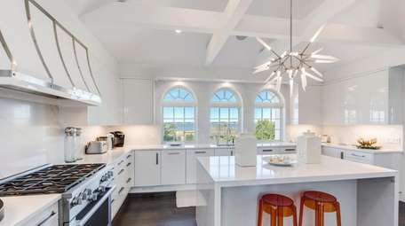 The chef's kitchen has a white-beamed cathedral ceiling,