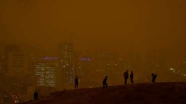 People look toward the skyline obscured by wildfire