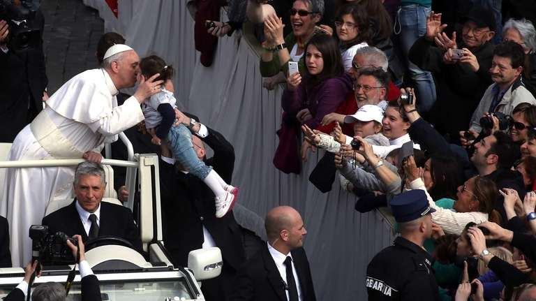 Pope Francis greets a child from an open-air