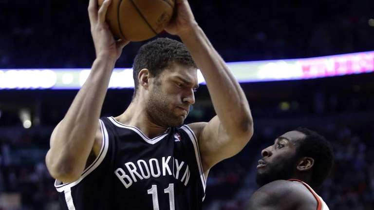 Nets center Brook Lopez, left, works the ball