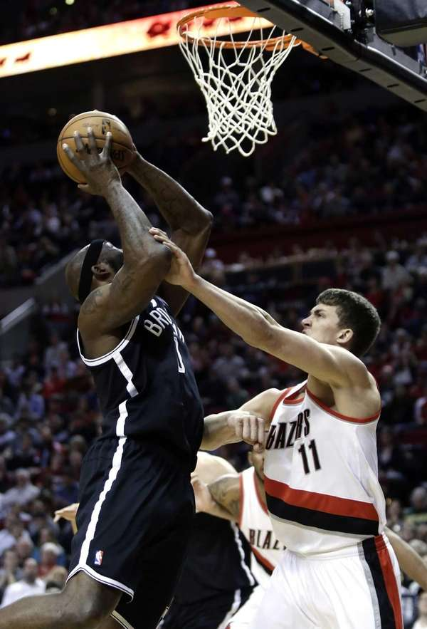 Nets forward Reggie Evans, left, is fouled while