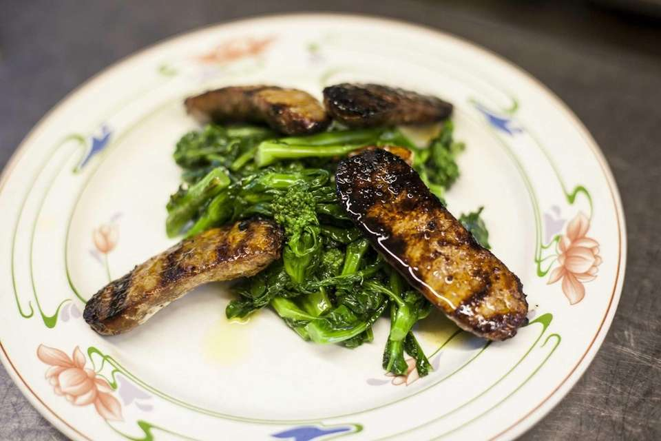 An appetizer of grilled sausage and broccoli rabe