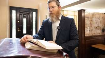 Rabbi Mendy Heber reads through passages in the