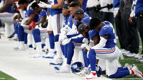 The Giants stand and kneel during the national