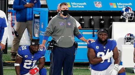Giants head coach Joe Judge stands with Jabrill