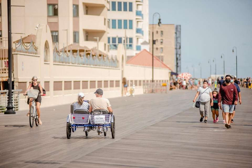 Beachgoers walk and bike along the Long Beach
