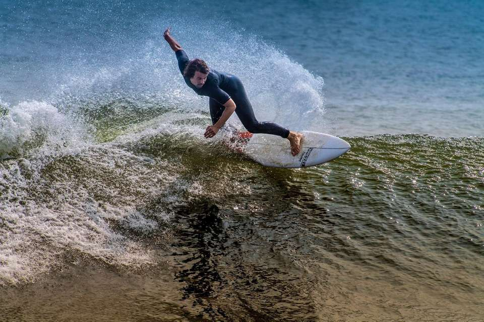 A surfer rides a wave in Long Beach,