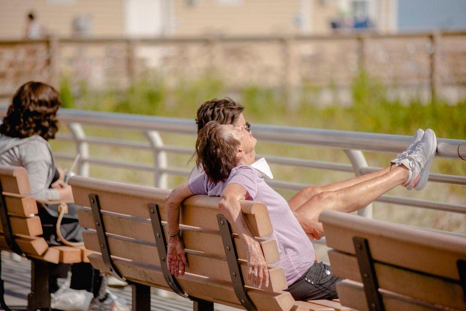Beachgoers bask in the sun on the Long