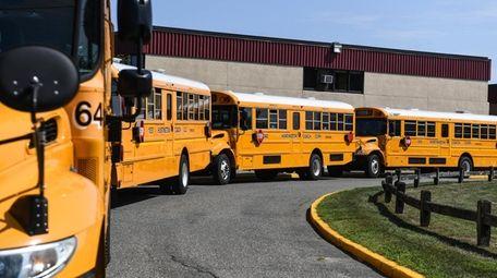 Busses wait outside Harborfields High School in Greenlawn