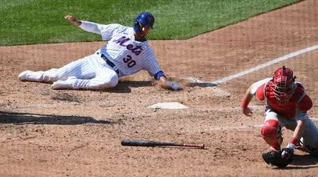 The Mets' Michael Conforto slides home behind Phillies