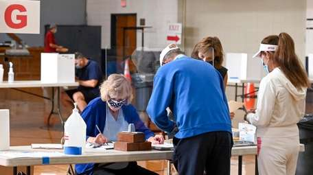 Voters sign in to vote in the auditorium