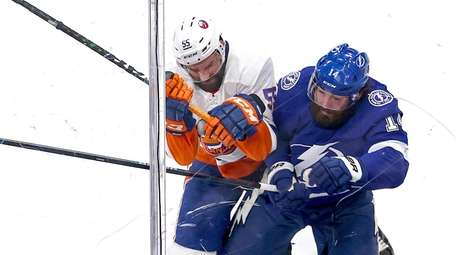 Johnny Boychuk of the Islanders checks Pat Maroon