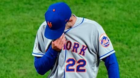 Mets pitcher Rick Porcello wipes his face during