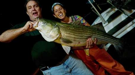Mike Sweeney holds a 30-pound striped bass caught