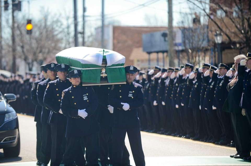 The NYPD Honor Guard carries the coffin during