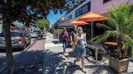Pedestrians in downtown Farmingdale on June 13.