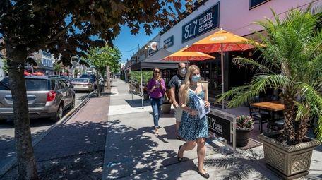 People walk in downtown Farmingdale on June 13.