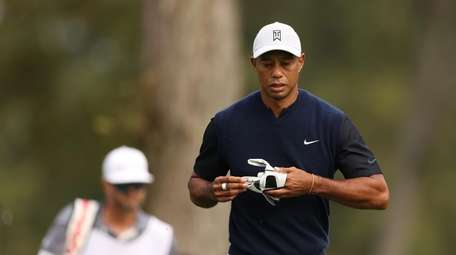 Tiger Woods walks off the eighth tee during