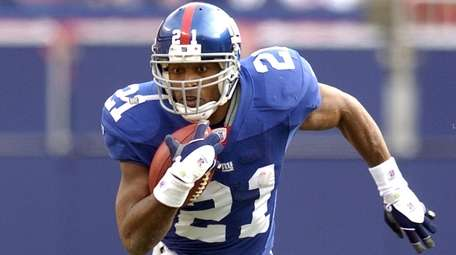 Tiki Barber runs in the first half against