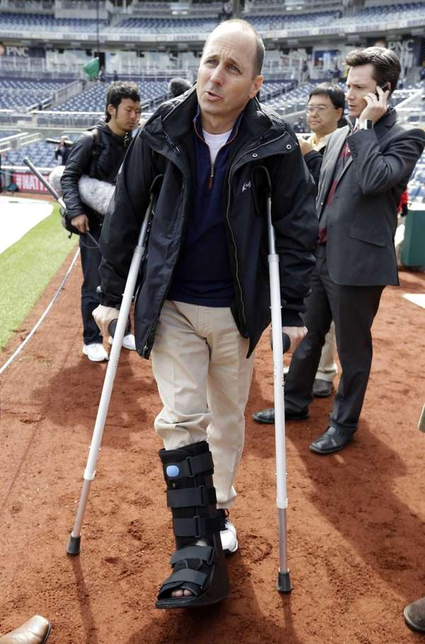Yankees general manager Brian Cashman stands on crutches,
