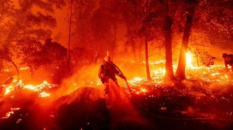 A firefighter battles a blaze that threatens homes
