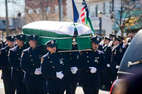The NYPD Honor Guard walks the coffin to