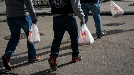 People carry plastic bags during the lunch hour