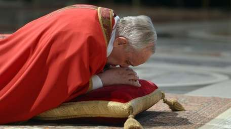 Pope Francis lies on the ground during the