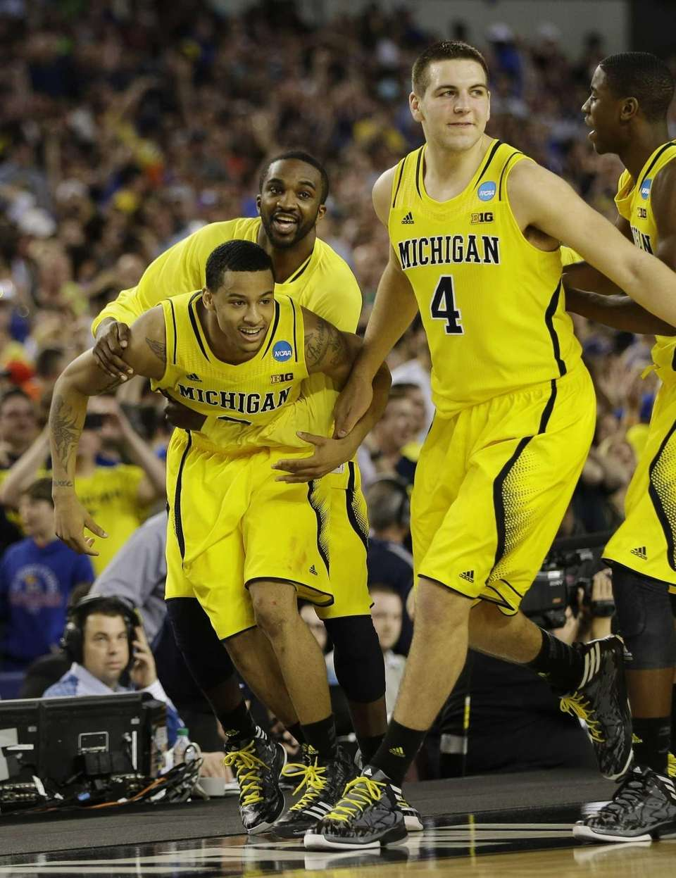 Michigan's Trey Burke, left, Corey Person and Mitch