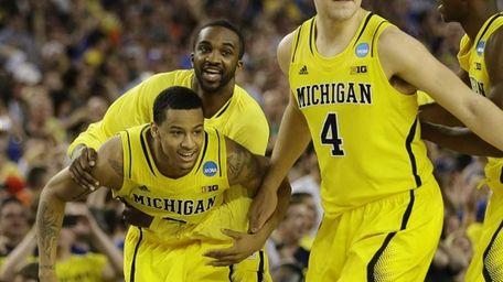 Michigan's Trey Burke, left, Corey Person and Mitch